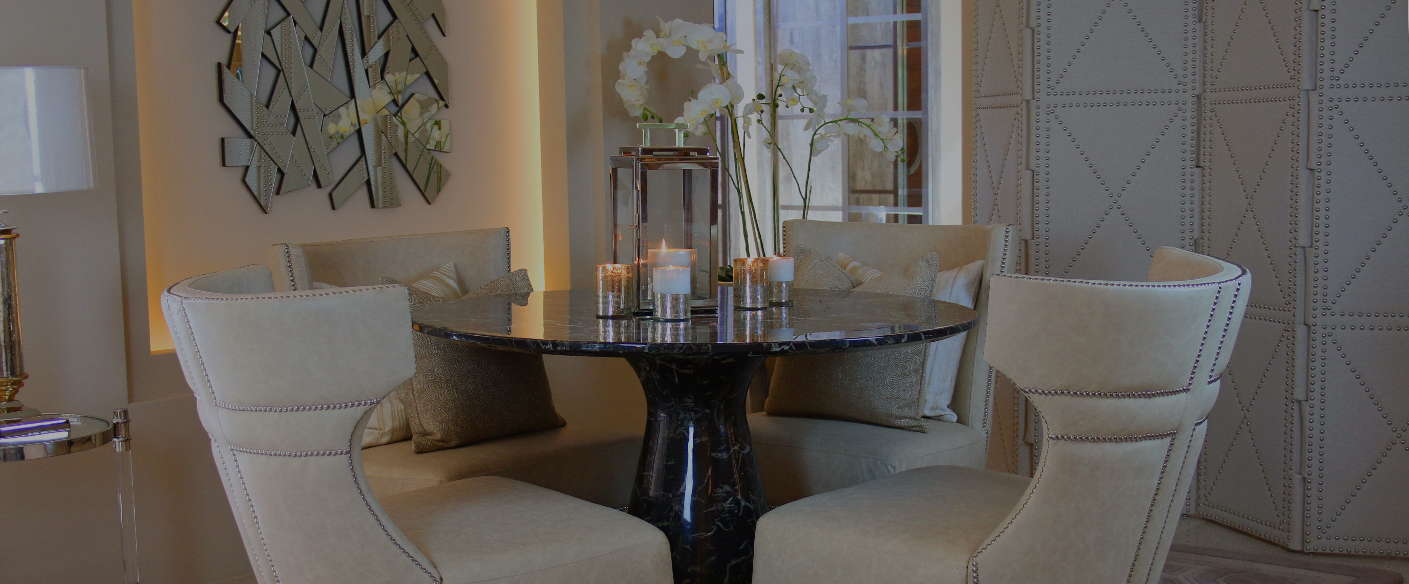 Marble table, cream studded chairs, inset wall art with back-lit lighting