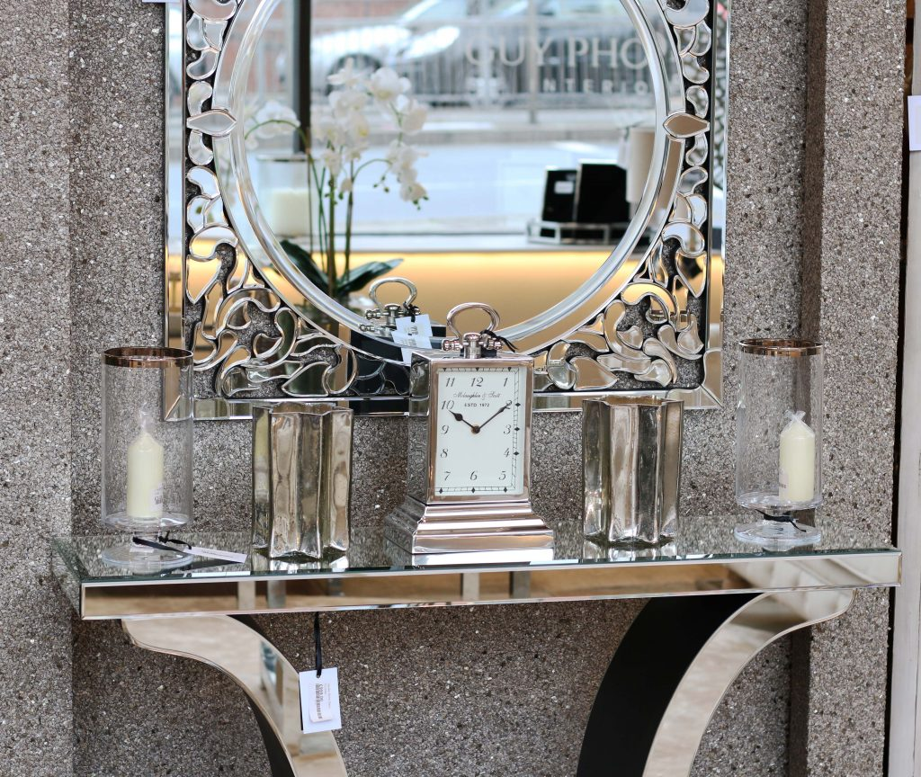 Sideboard with silver carriage clock, candles and decorative circle mirror